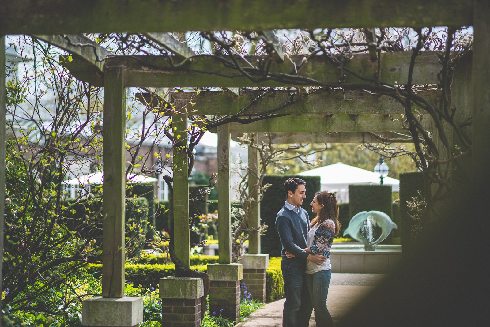 Engaged Couple chat surrounded by the vine trellis at the Hurlingham Club