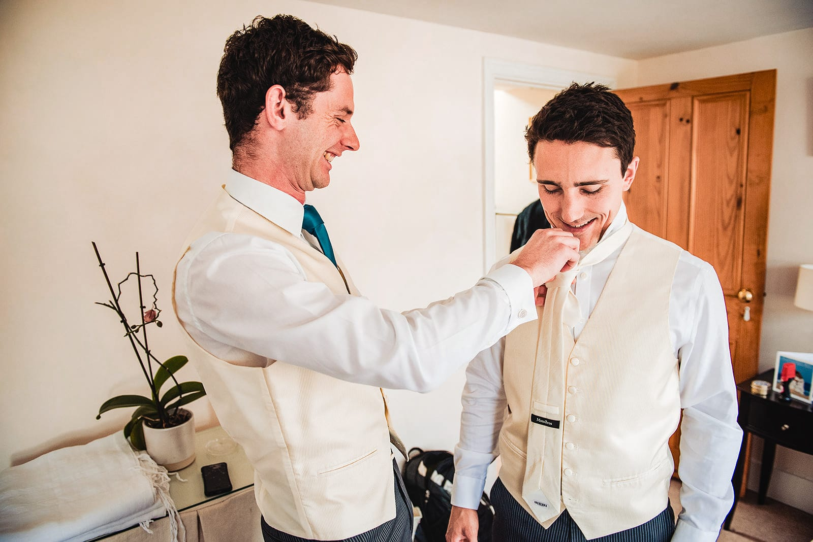Groom and his best man laugh as he puts on his tie the wrong way round
