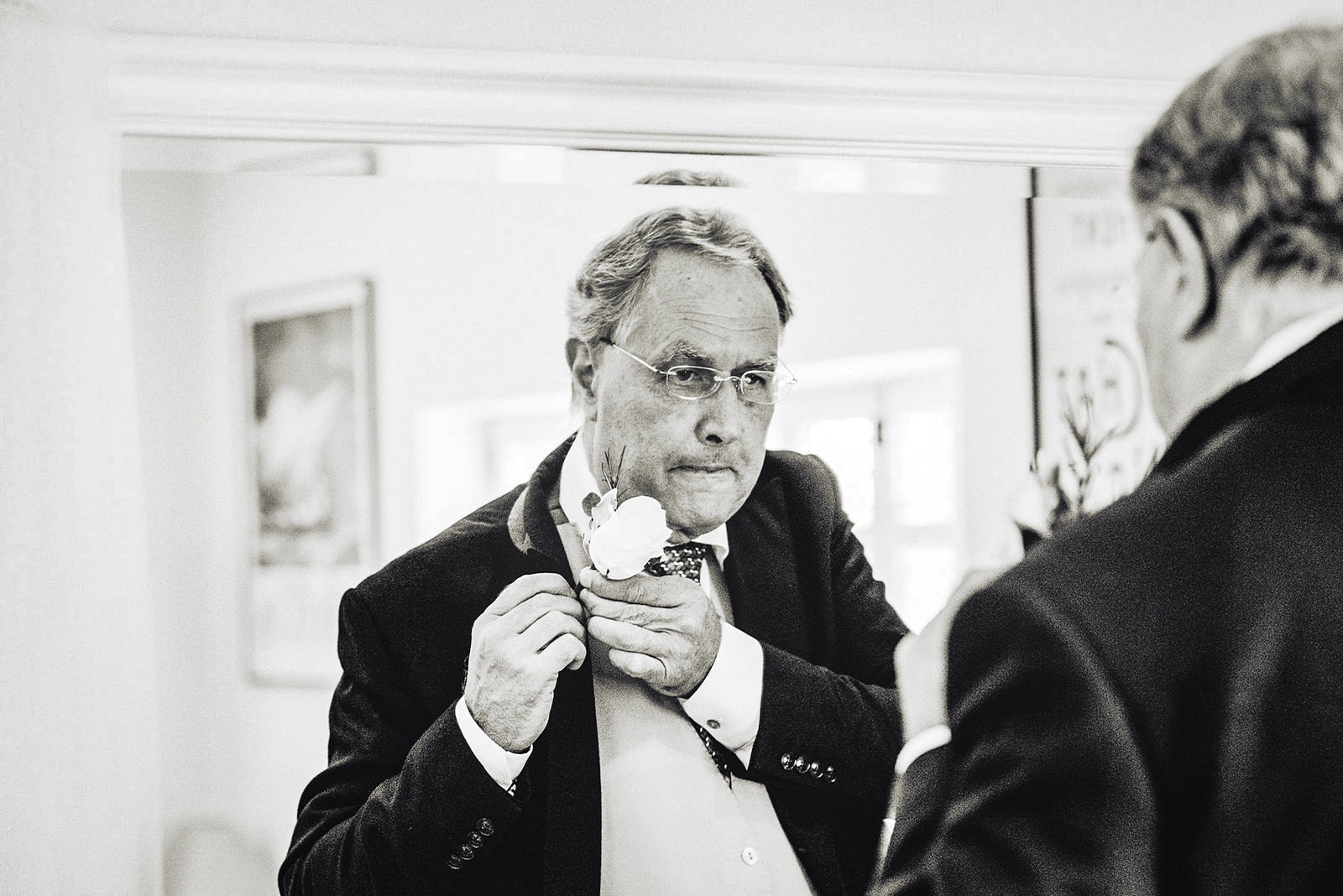 The father of the bride putting on his white rose boutonnière