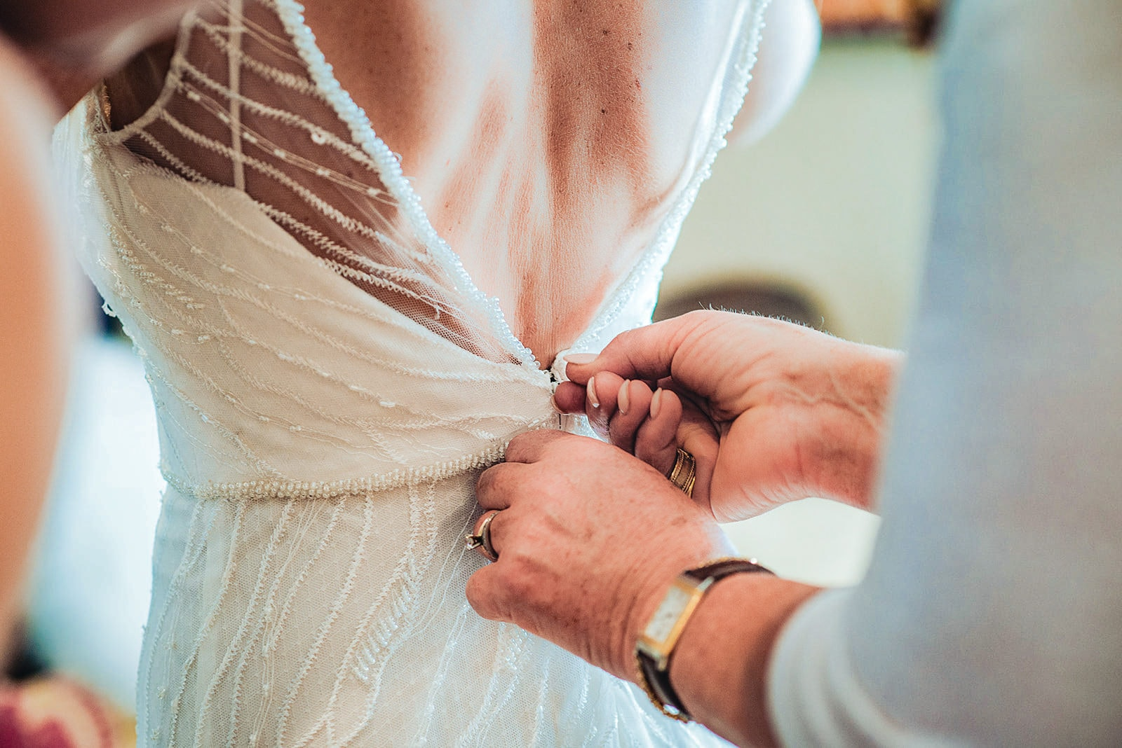 Mum fastening the bride's bead and lace wedding dress