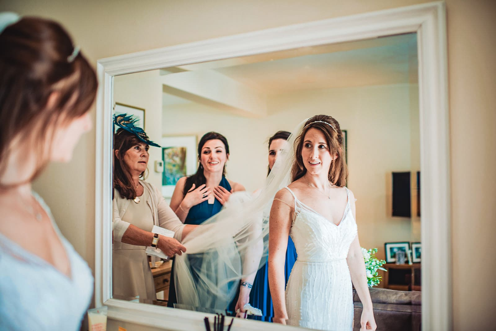 Bride smiles at her bridesmaids as her mum puts on her wedding veil