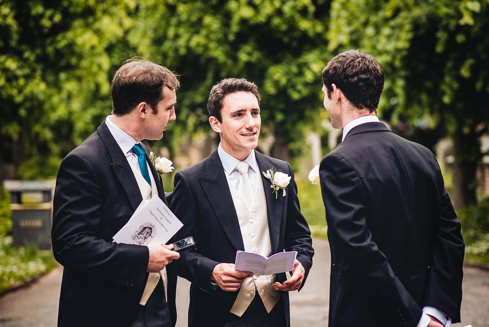 Groom chat's with his groomsmen outside Fulham All Saints Church