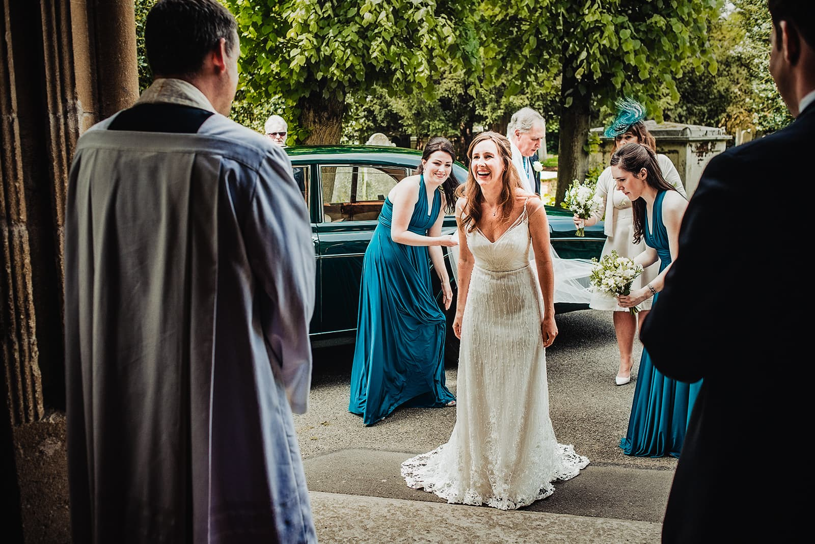 Bride smiles at the vicar as she arrives at her Fulham All Saints Church wedding ceremony