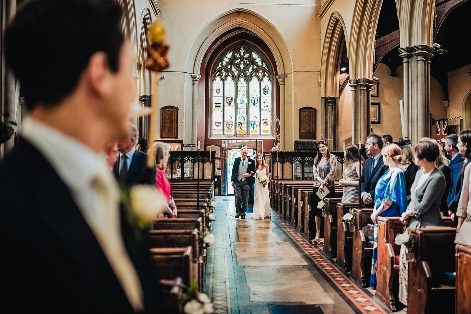Bride walks down the aisle at All Saints Church in Fulham with her dad smiling at her groom