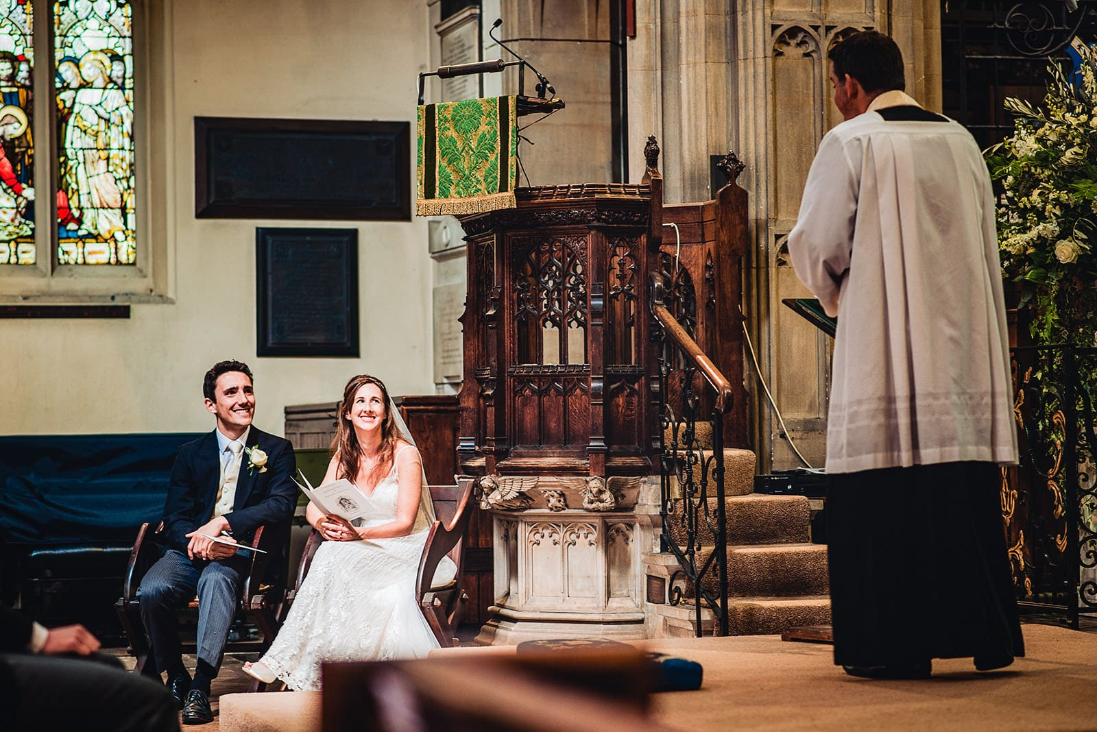 Bride and groom smile as their vicar delivers his wedding sermon