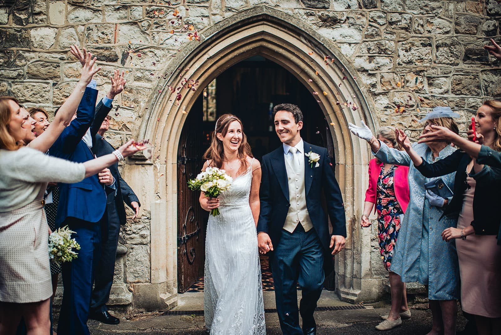 Bride and groom exit All Saints Church in Fulham under rose petal confetti