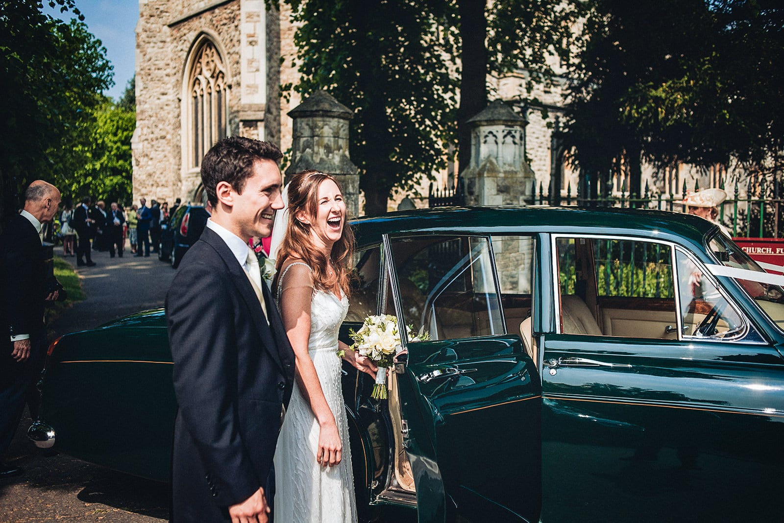 Bride and groom laugh as they get in their vintage wedding car at All Saint's Church, Fulham