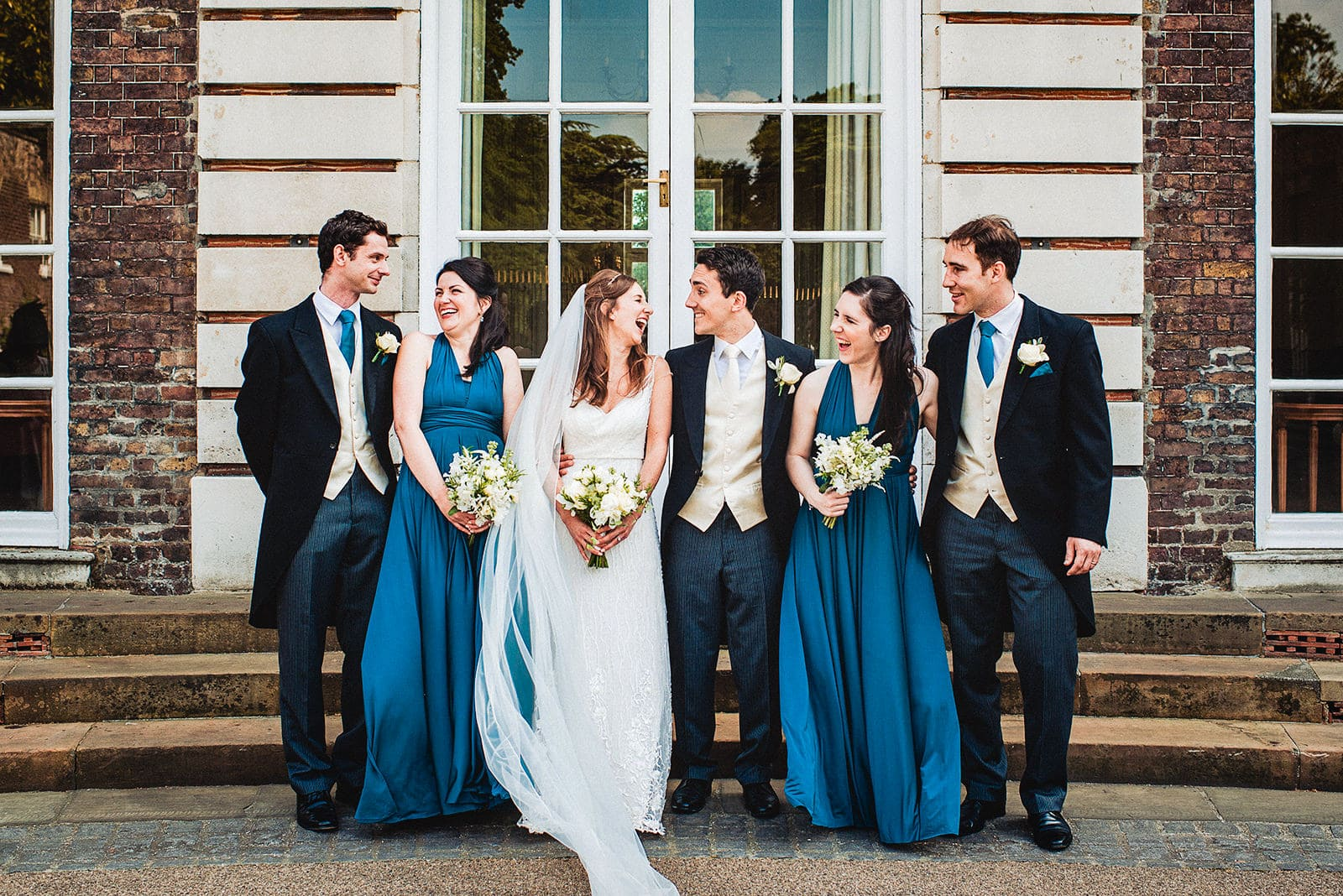 Bride and groom, teal bridesmaids and groomsmen laugh outside the Hurlingham Club