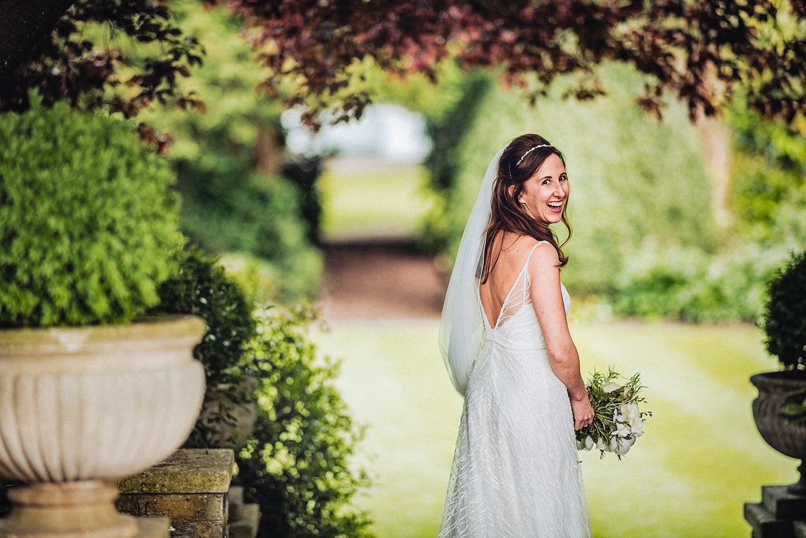 Bride laughs over her shoulder at her summer Hurlingham Club wedding