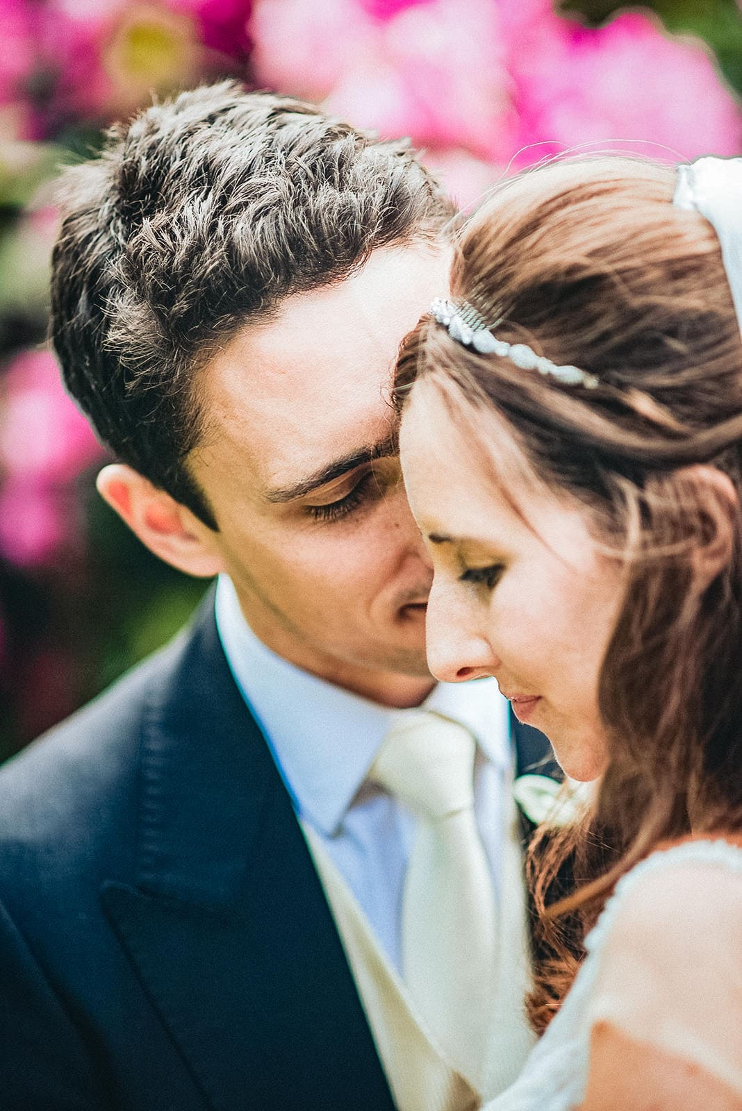 Groom kisses the bride's cheek with pink flowers at the hurlingham Club behind them