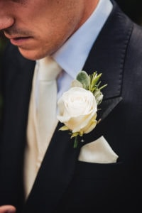 Close up of the Groom and his white rose boutonniere buttonhole