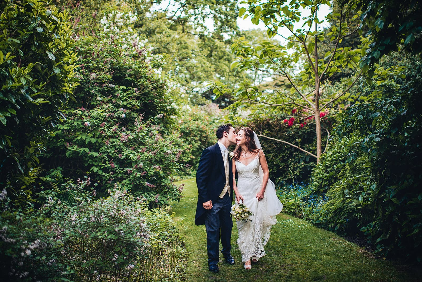 Bride and groom walk through the Hurlingham Club's sunken garden