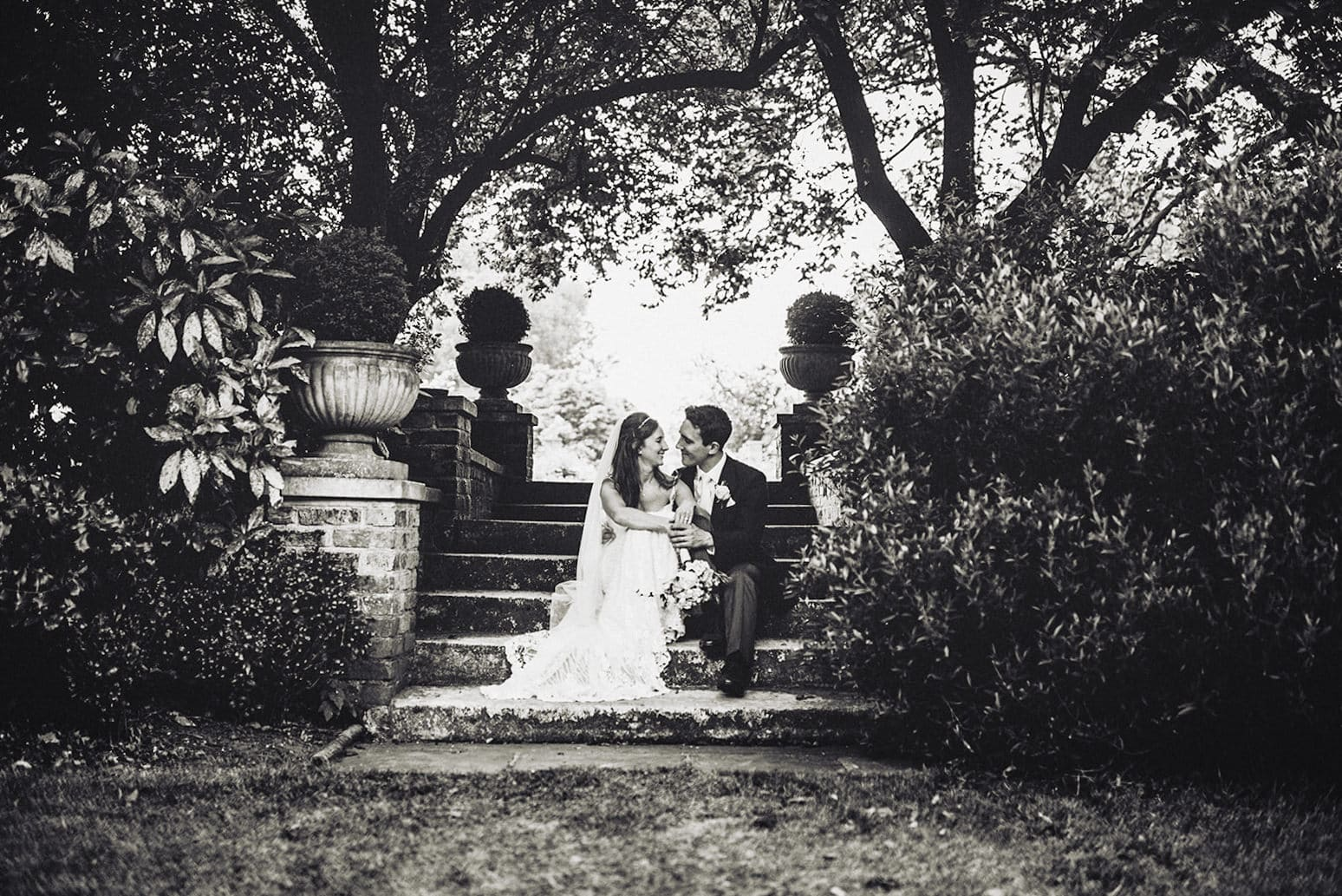 Bride and groom sit on the steps at the Hurlingham Club's sunken garden
