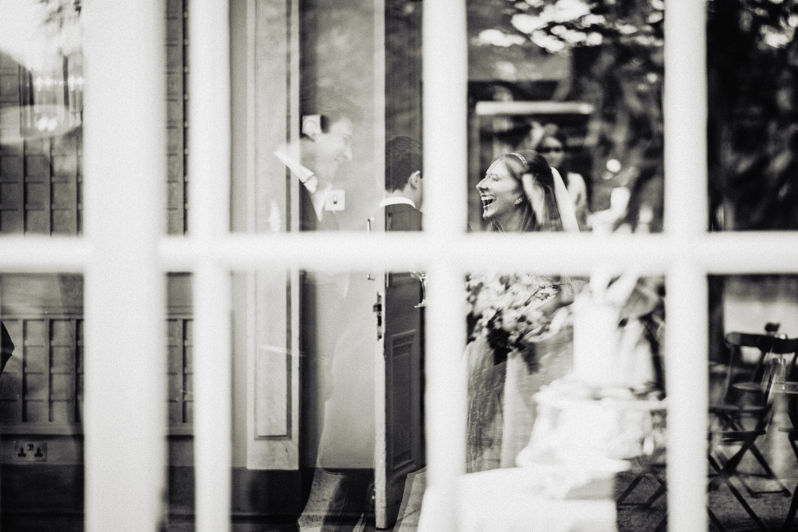 Reflection of the bride laughing with her guests at her summer Hurlingham Club wedding