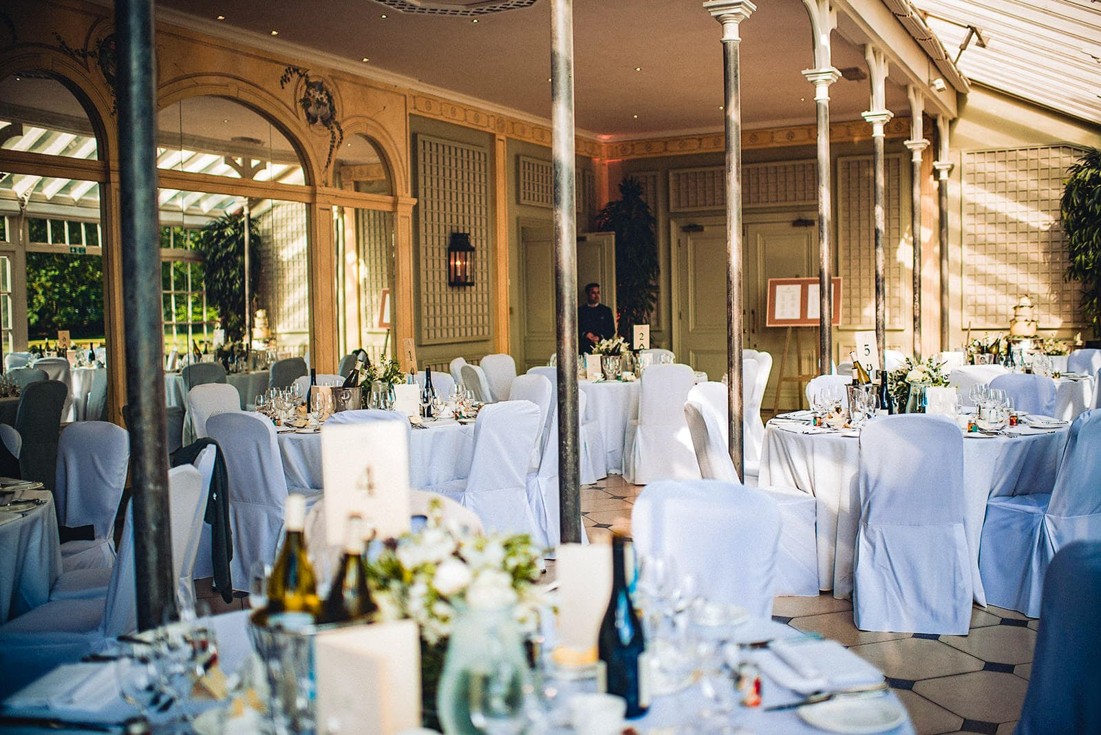 The Terrace Room at the Hurlingham Club set up for an elegant white wedding breakfast