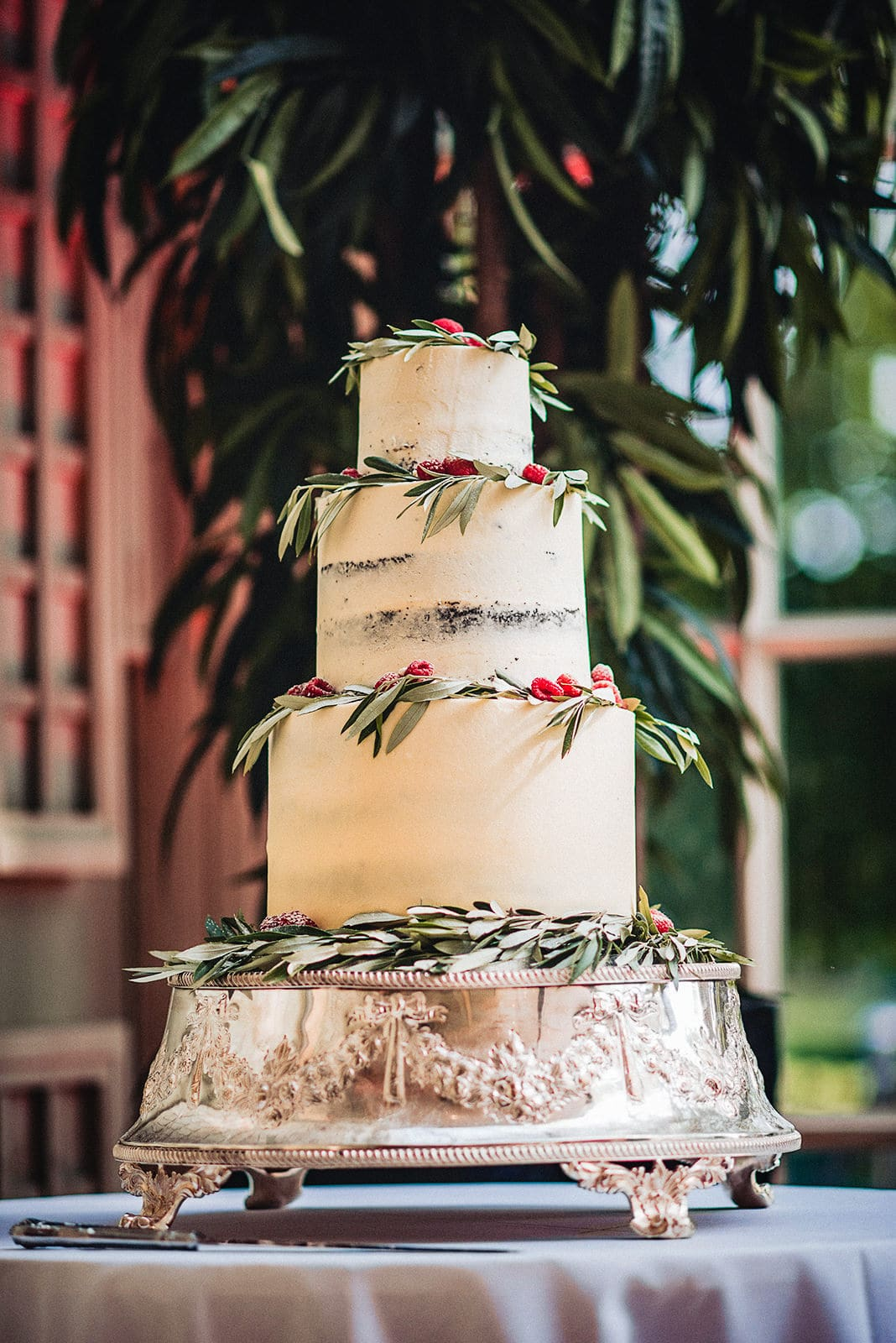 Semi-naked wedding cake with eucalyptus leaves and fresh raspberries