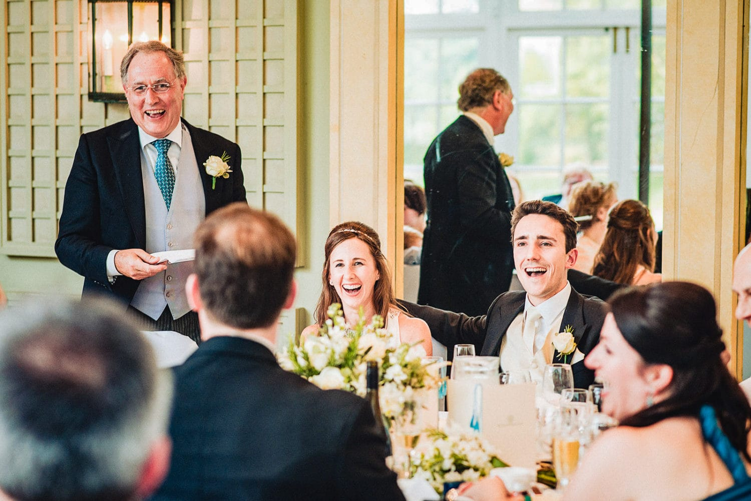Bride and groom laugh at the Father of the bride's speech at the Hurlingham Club