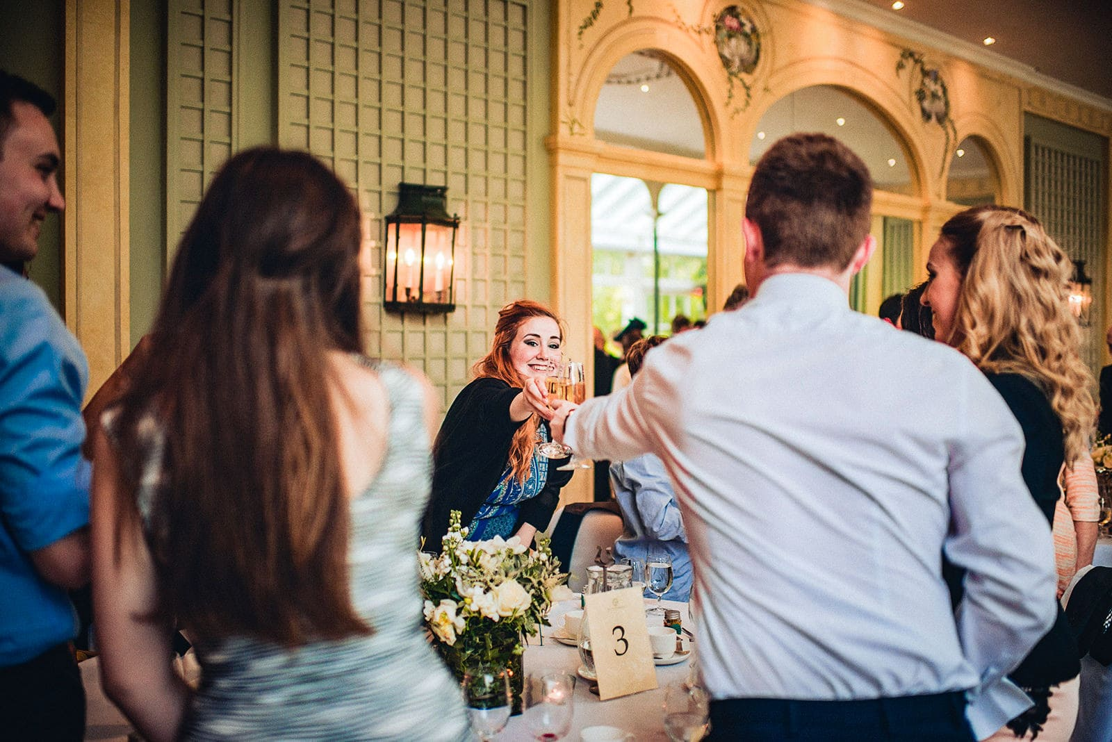 Wedding guests cheer with drinks at the Hurlingham Club