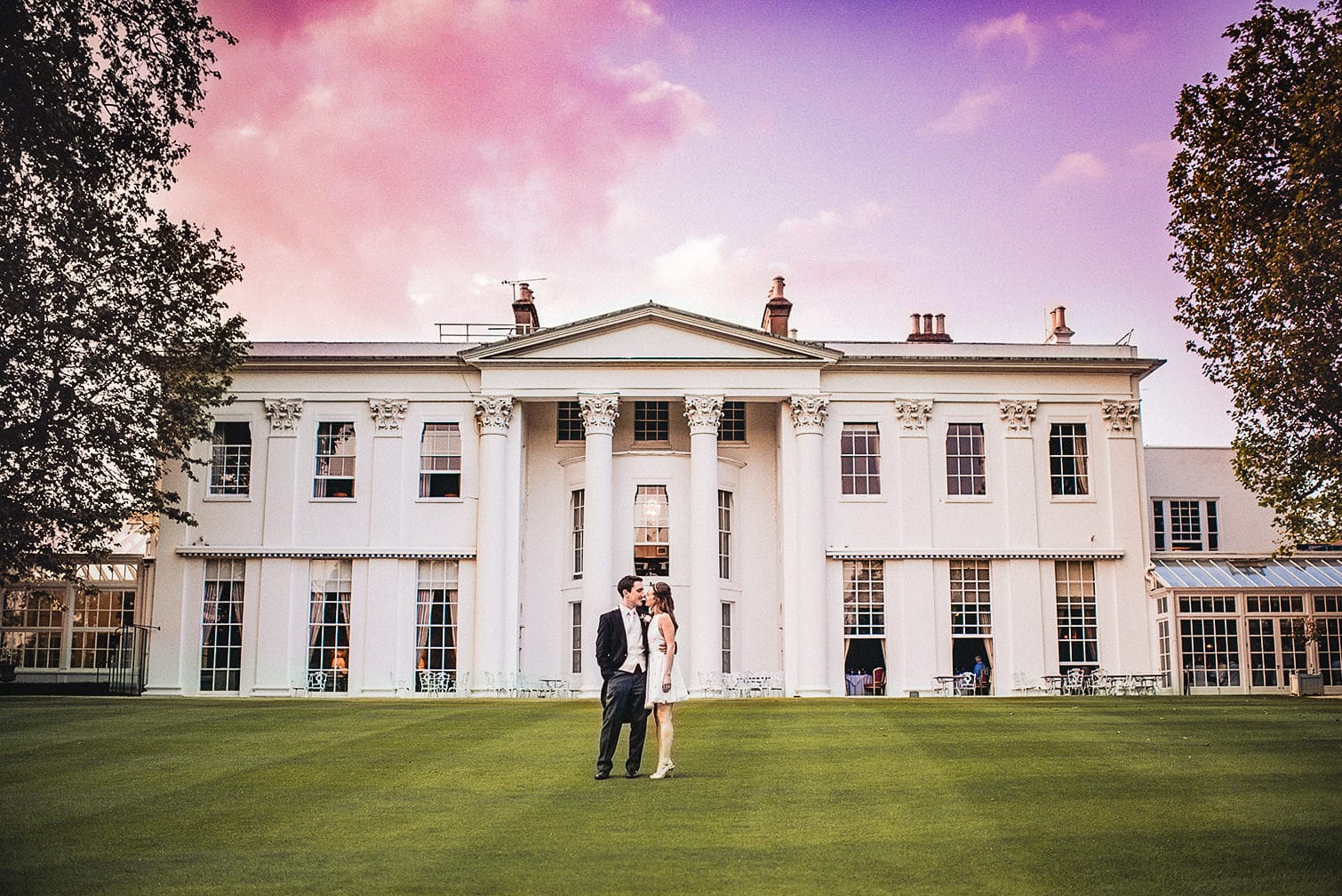 Bride and groom standing on the green at sunset at the Hurlingham Club