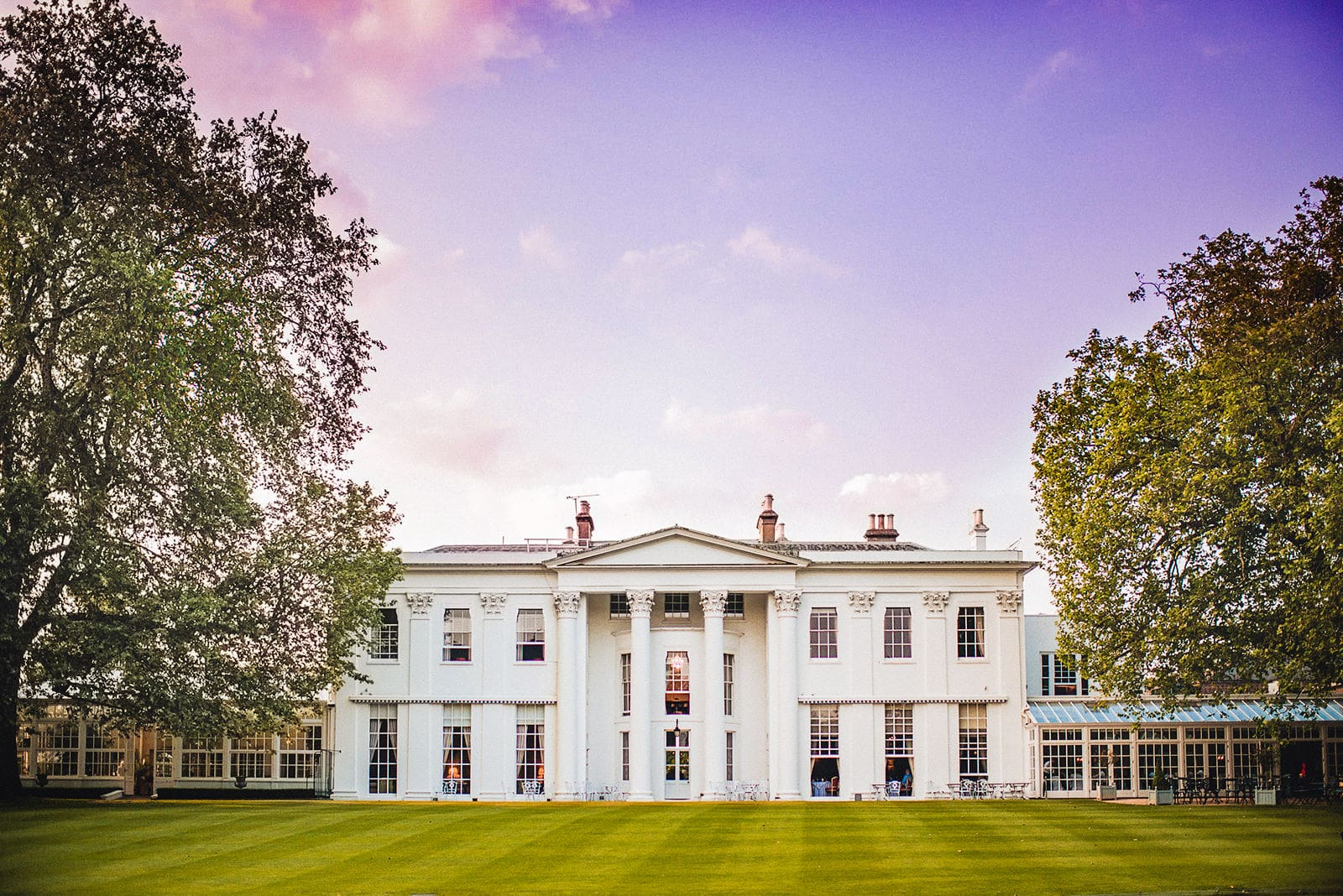 The Hurlingham Club and lawns with a pink sunset sky