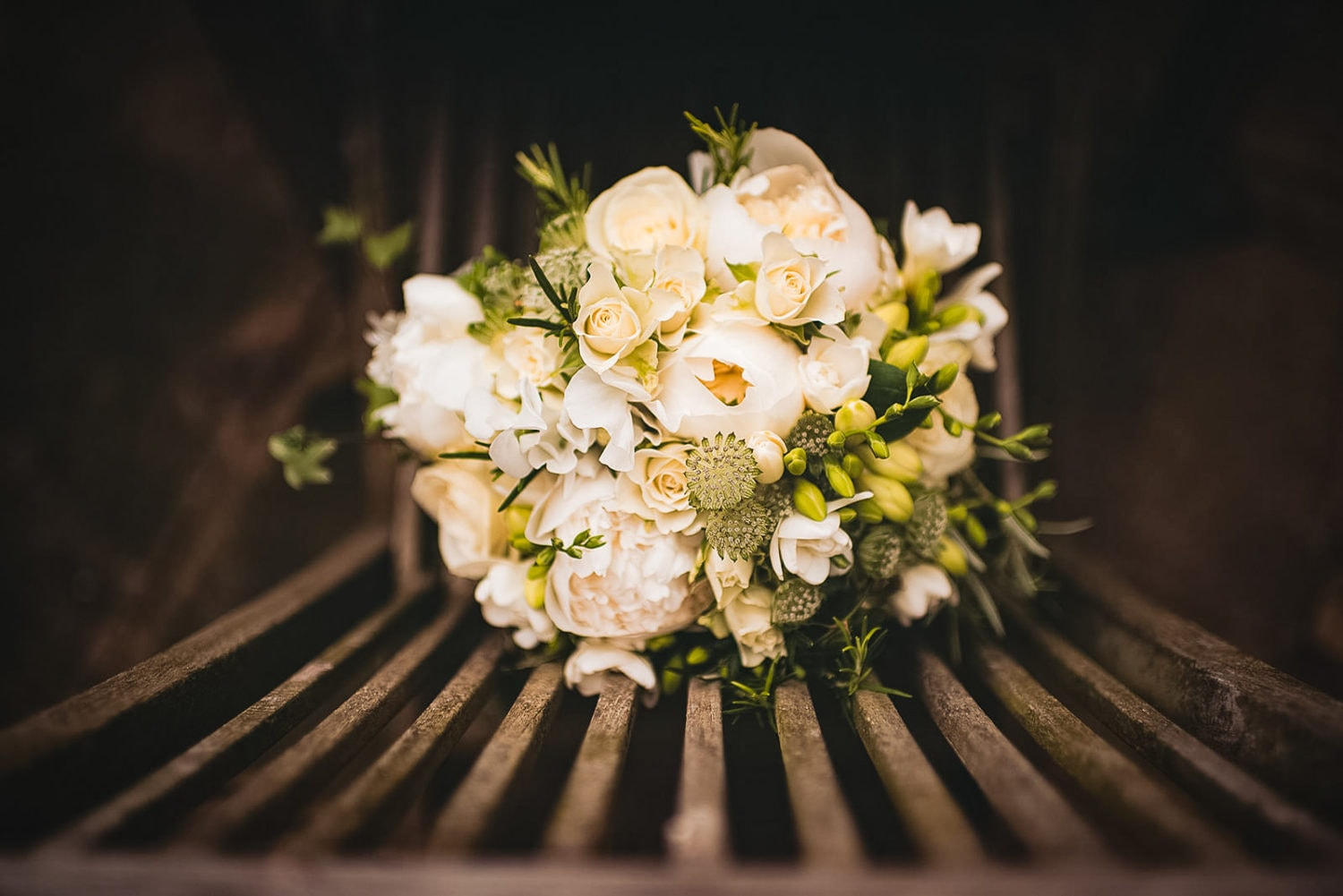 White wedding bouquet with white roses, fresias and peonies