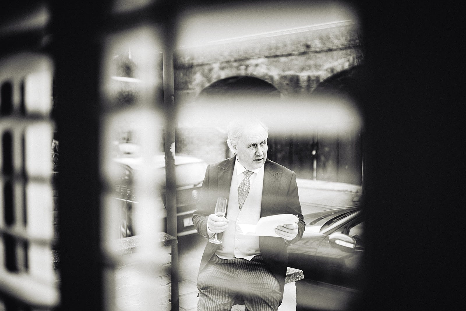 Father of the bride practicing his wedding speech seen through a shuttered window