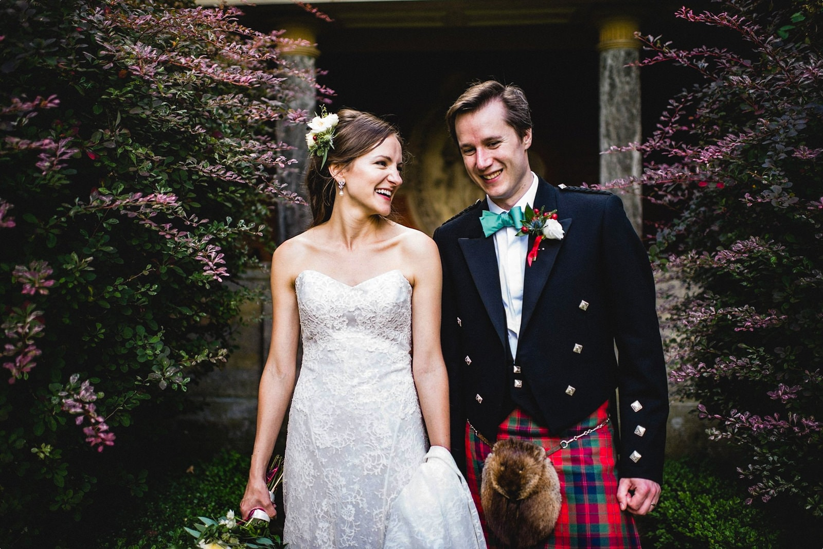Bride and Scottish groom in a kilt walk together laughing