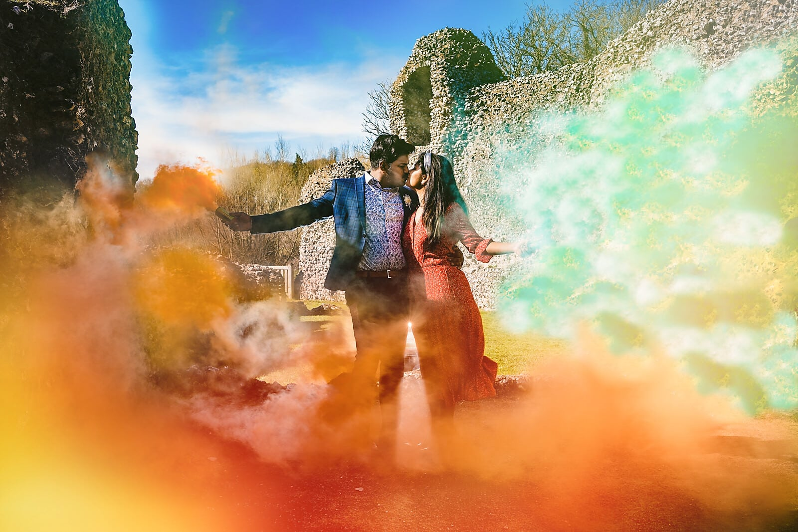 Engaged couple kiss surrounded by orange and green smoke from smoke bombs