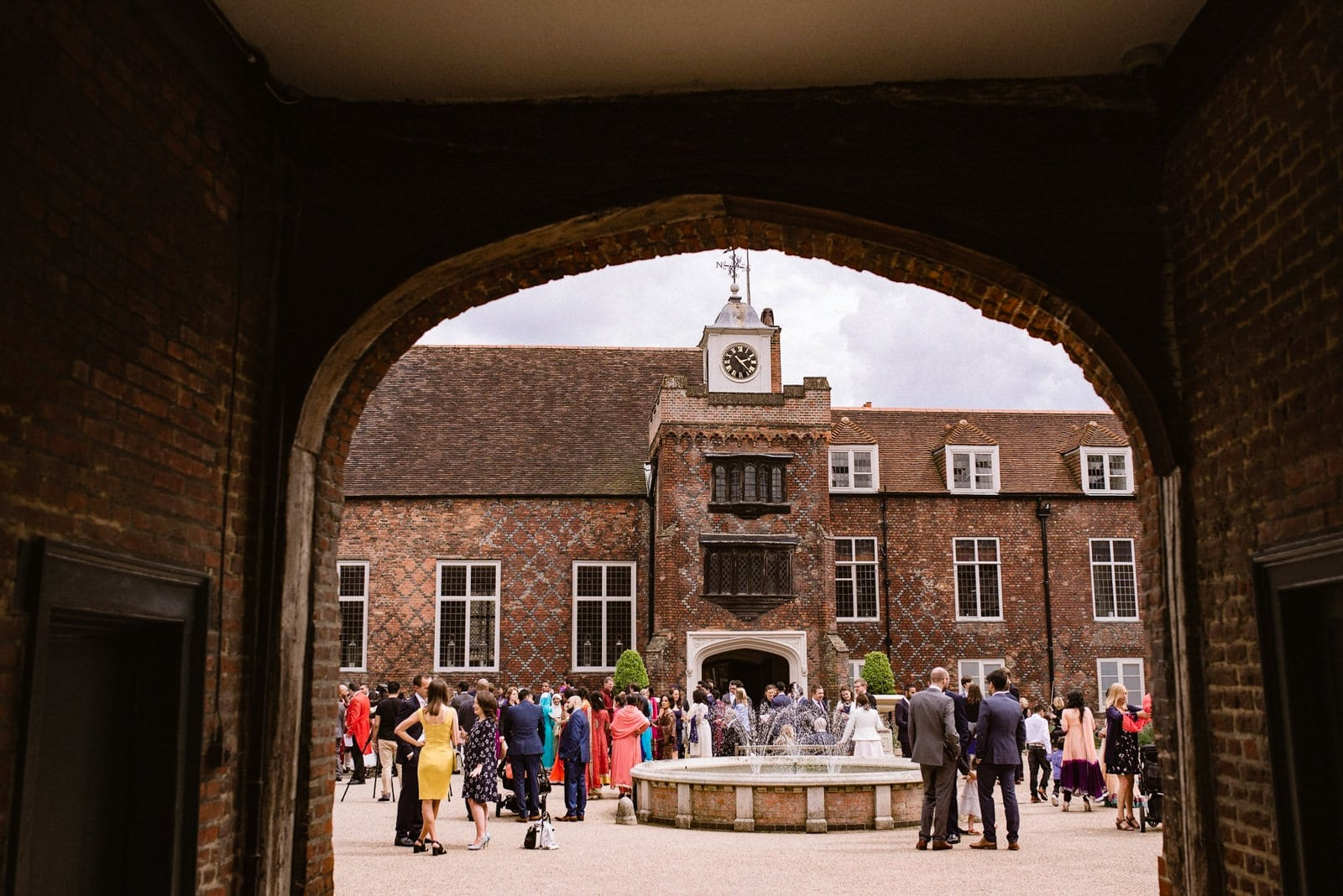 Wedding guests chat in the courtyard of Fulham Palace