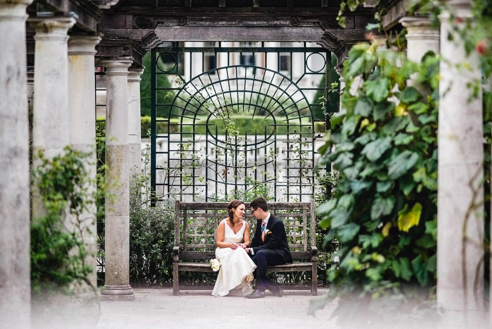 Bride and groom sit and chat on a bench at the Hampstead Pergola and Hill Garden