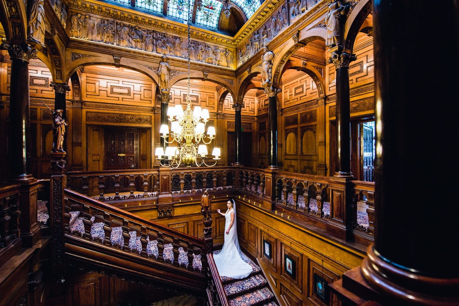Bride walks up the magnificent wooden staircase and gallery at Two Temple Place