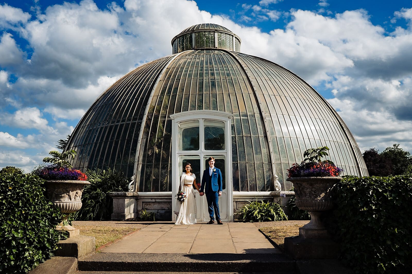 Bride and groom standing in front of the large Palm House at Kew Gardens