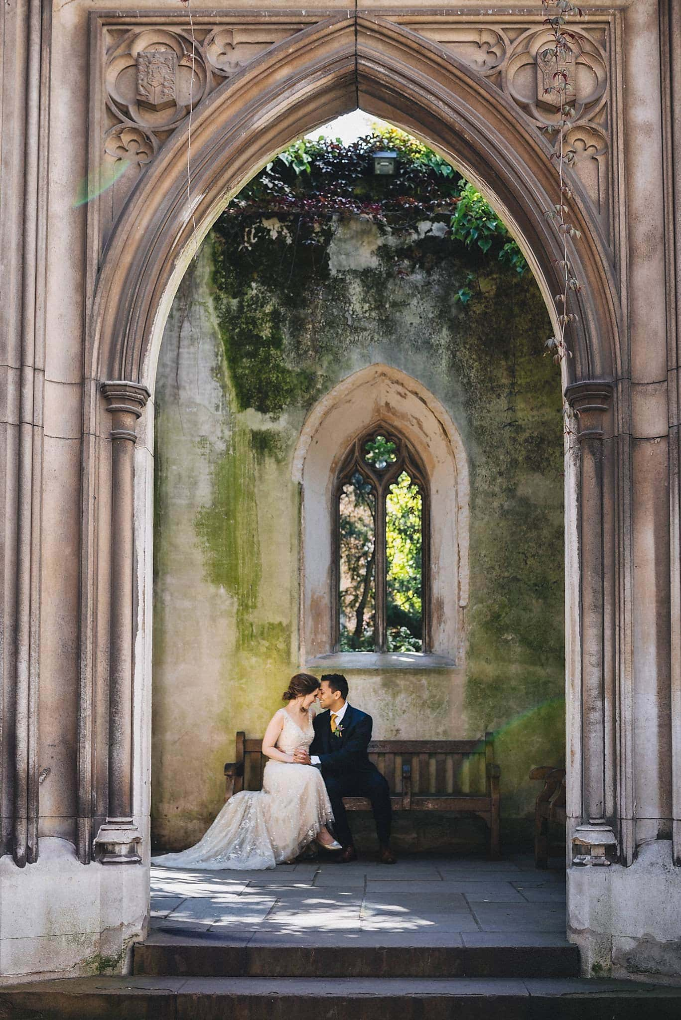 Bride and groom sit close on a bench at St Dunstan in the East in London