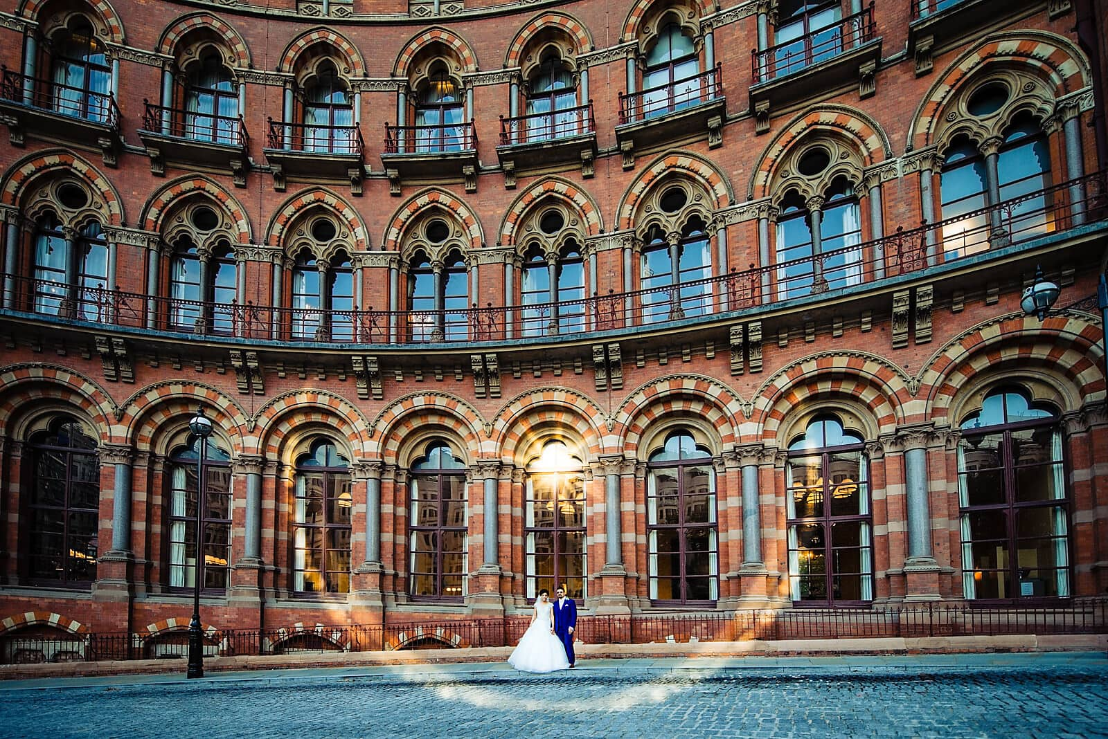 Bride and groom stand in front of the St Pancras Renaissance Hotel surrounded by a sunflare