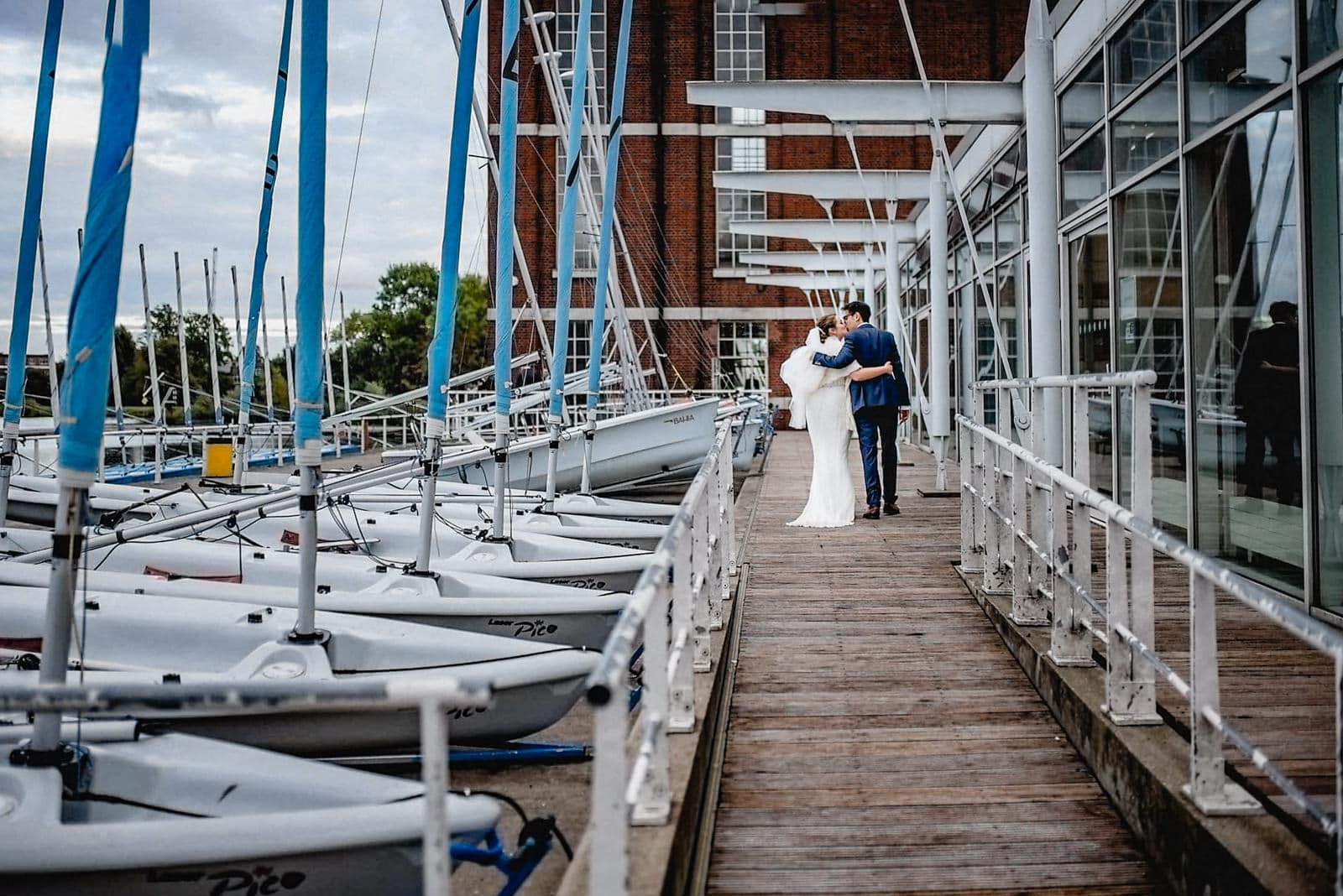 Bride and groom walk past the moored boats at the pier of the West Reservoir Centre