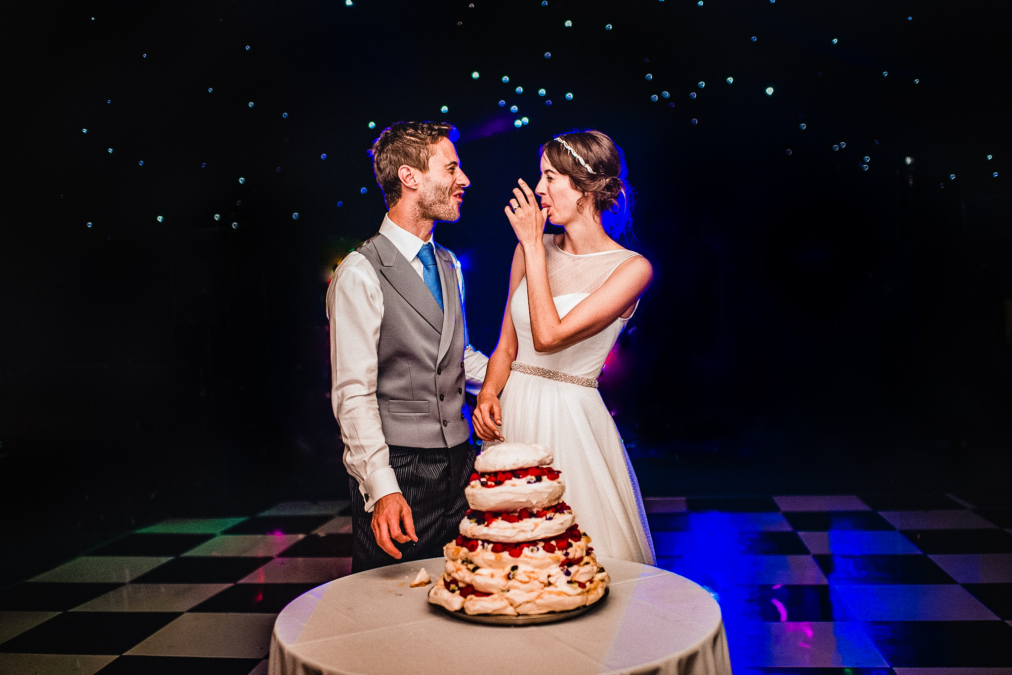 Bride and groom wink at each other after tasting their incredible strawberry pavlova wedding cake