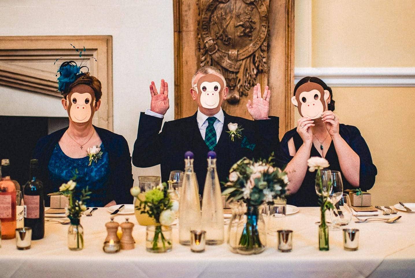 Wedding guests wear monkey masks at a monkey themed Farnham Castle Wedding