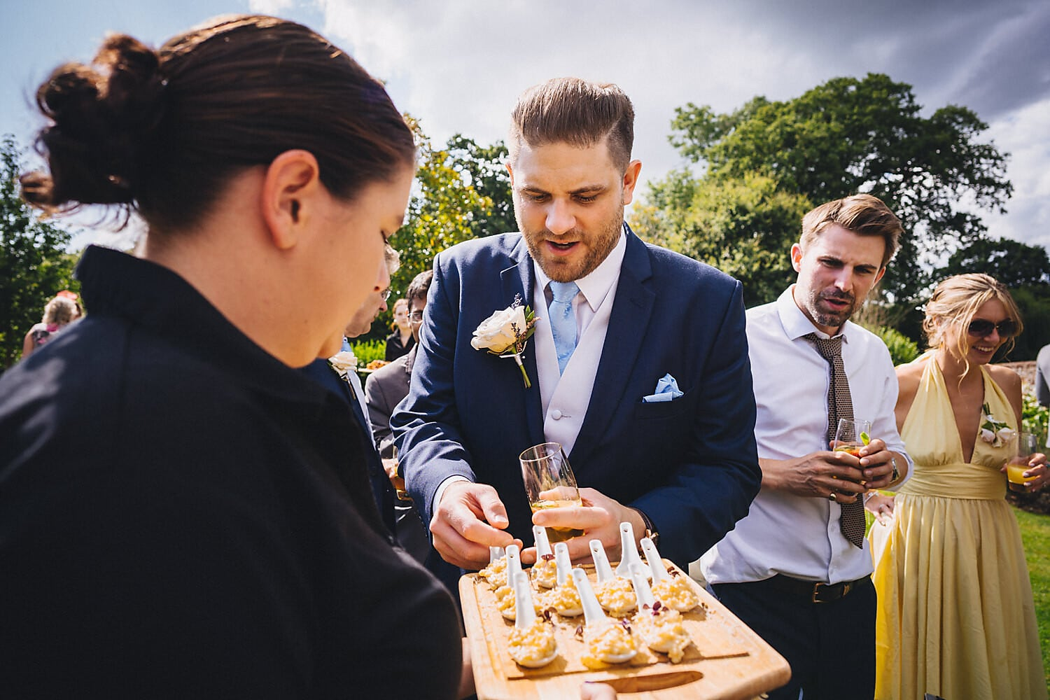 Wedding guests reaching for canapés