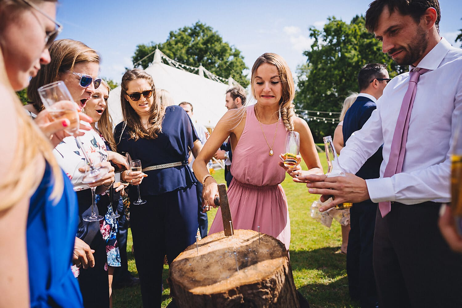Wedding guests react as a bridesmaid tries to hammer a nail into a log