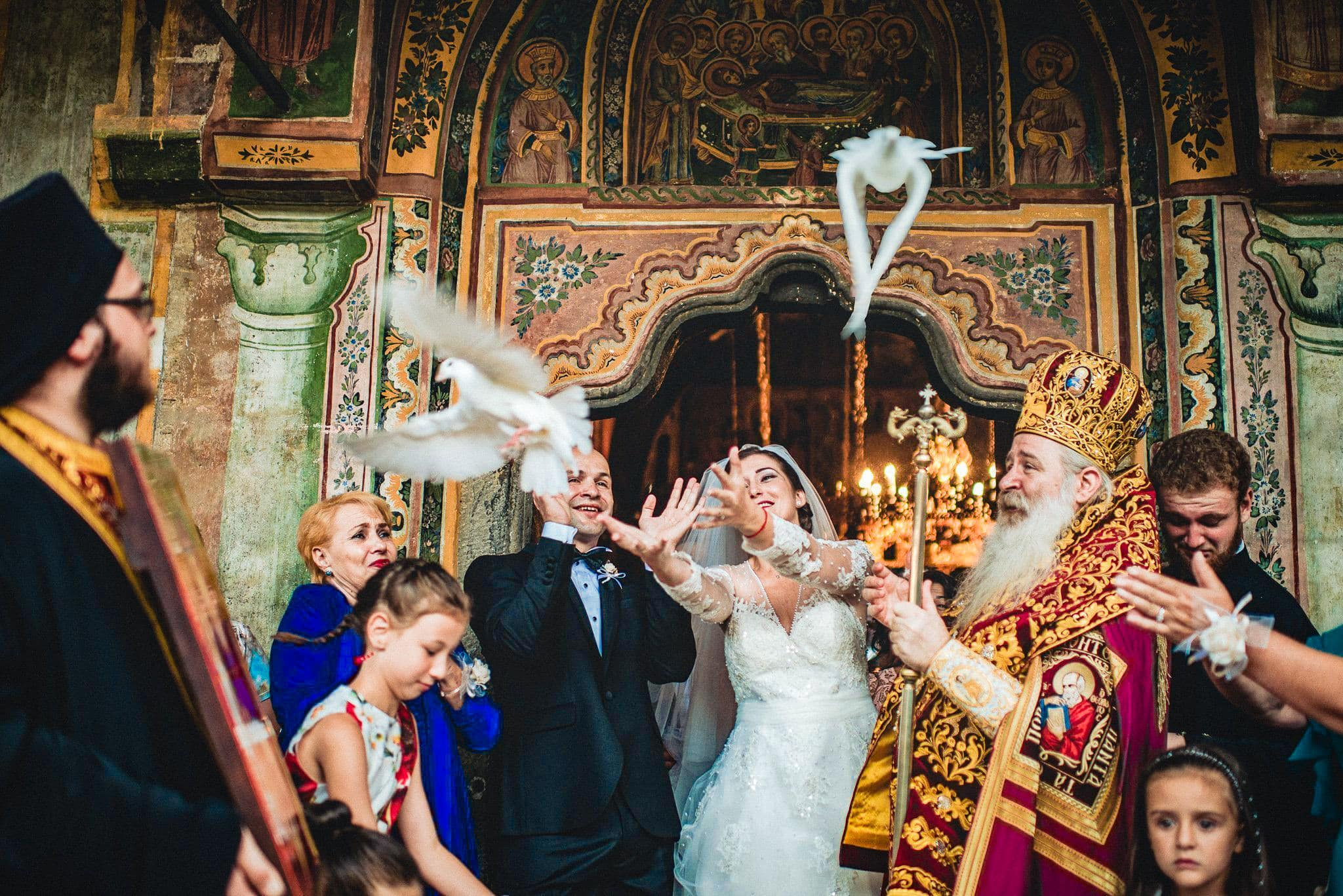 Bride and groom release white doves at a Bulgarian Monastery Christian Orthodox Destination Wedding