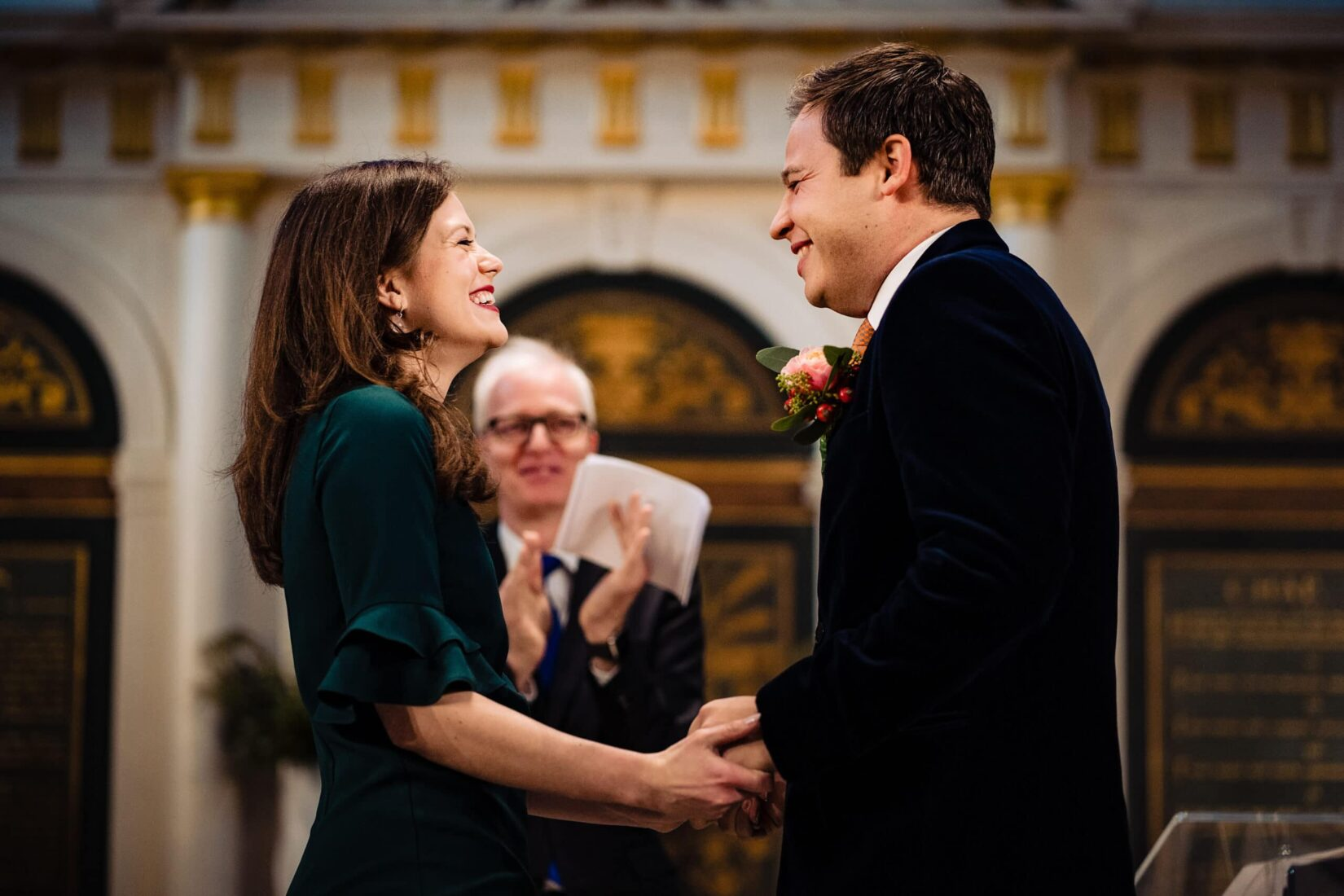 Bride and groom smile broadly at each other at their Saint James Clerkenwell wedding ceremony