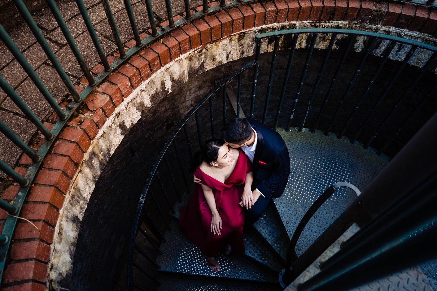 Asian couple sit on the spiral stairs at the Hampstead Pergola and Gardens