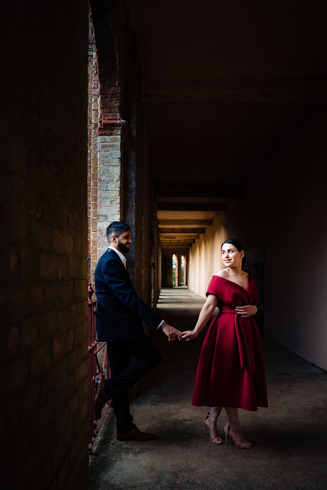 Asian couple hold hands in the arched pathway at the Hampstead Pergola and Gardens in London