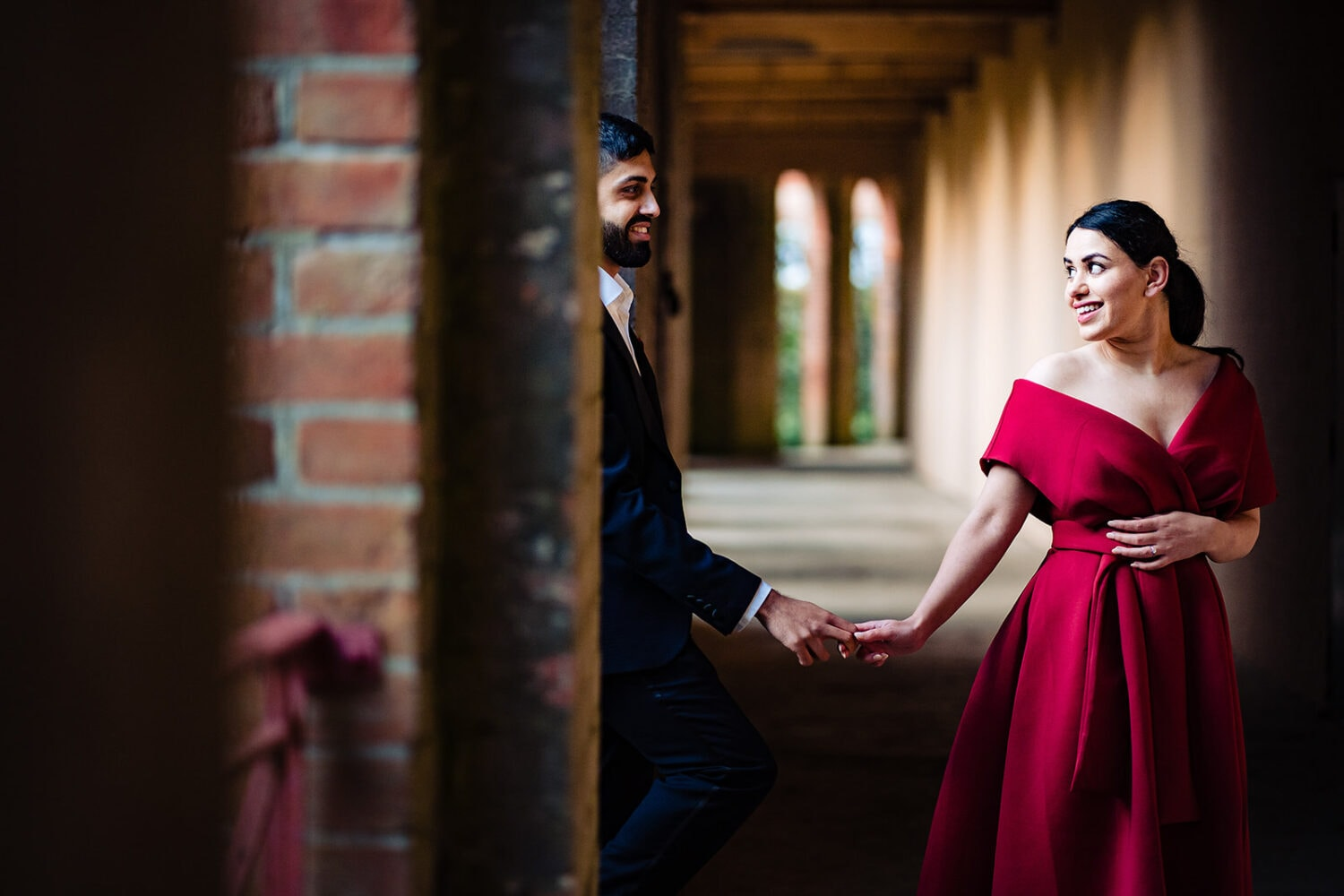 Asian couple smile holding hands at London's iconic Hill Garden and Pergola