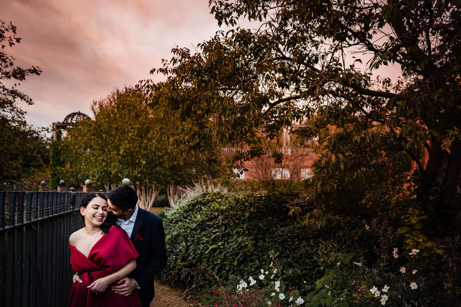 Asian Couple smile hugging with sunset skies in the gardens of the Hampstead Pergola