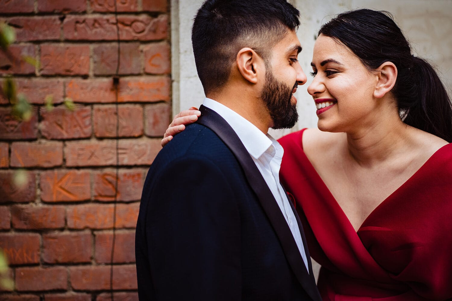 Asian couple smile at each other on their London engagement shoot