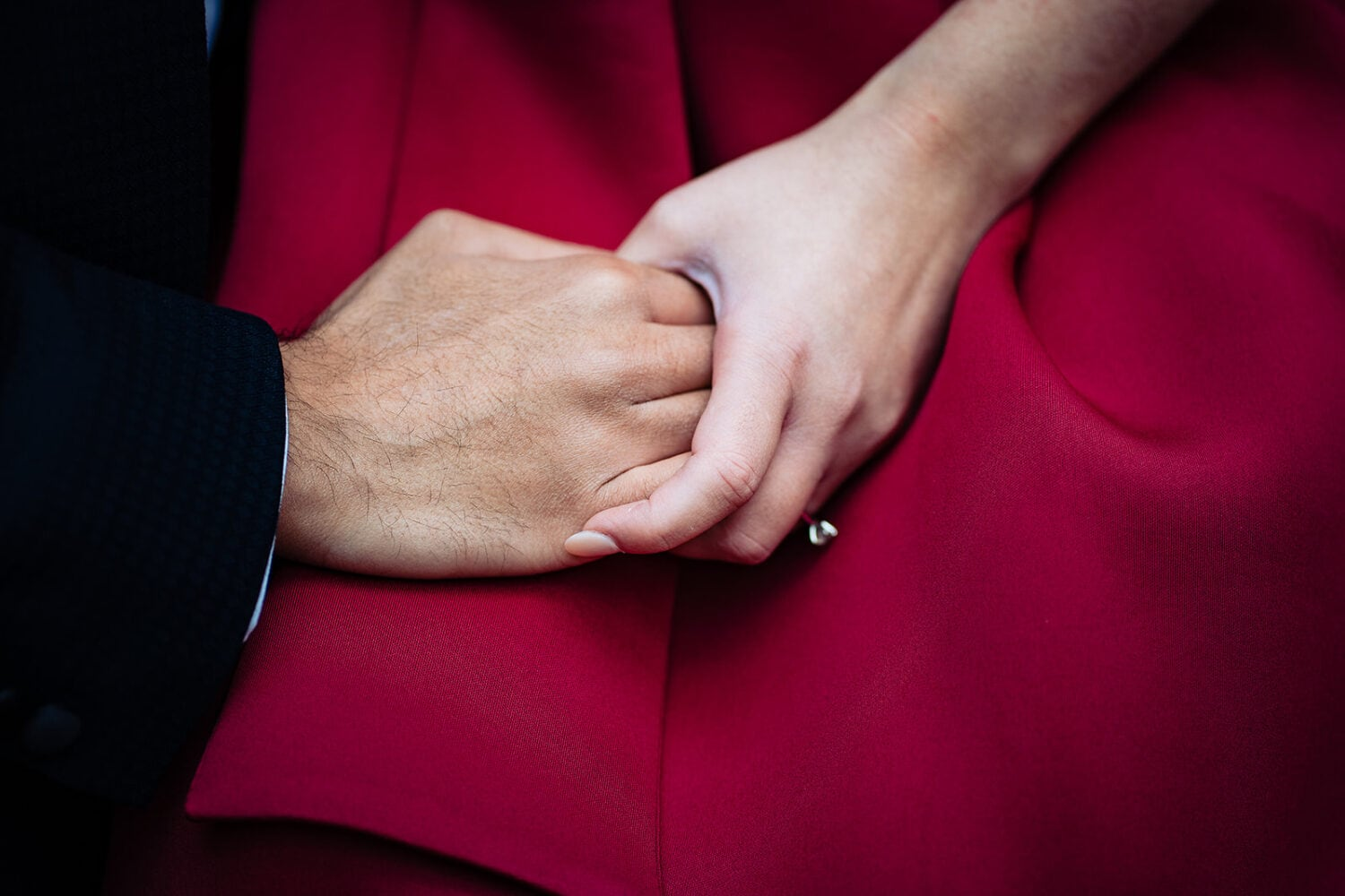 Asian couple holds hands with large diamond engagement ring on a red dress and navy suit