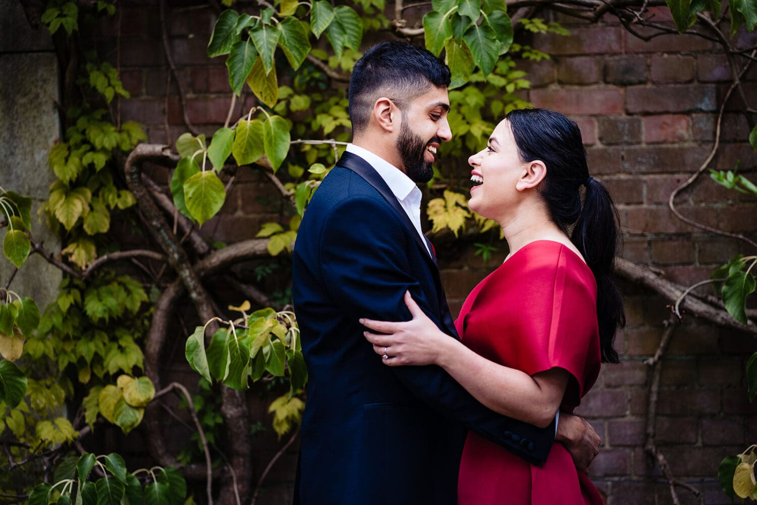Couple laugh and embrace at their London Hill Garden and pergola engagement