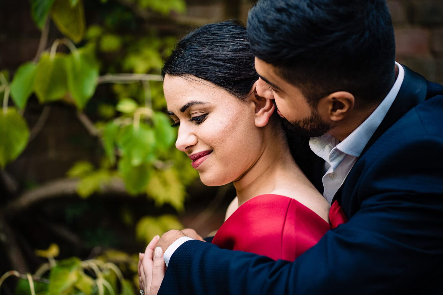 Asian Groom whispers in bride's ear as they embrace at London's Hampstead Pergola