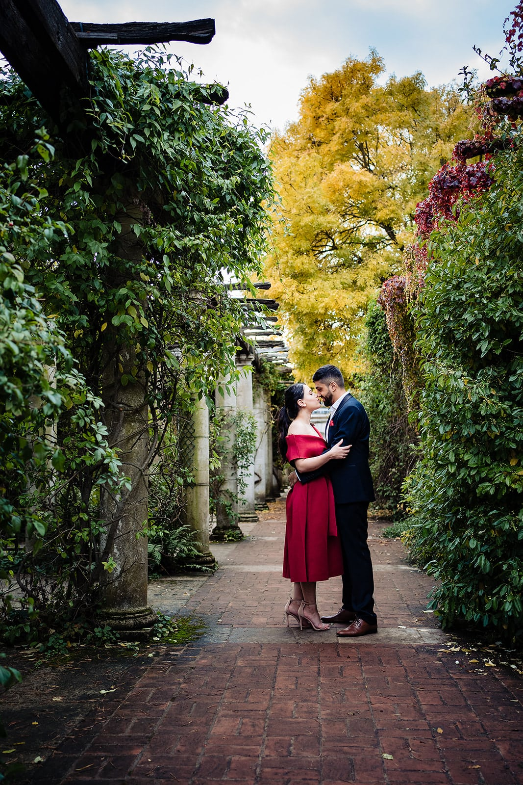 Couple kiss in the column-framed walkway at London's Hill Gardens and Pergola